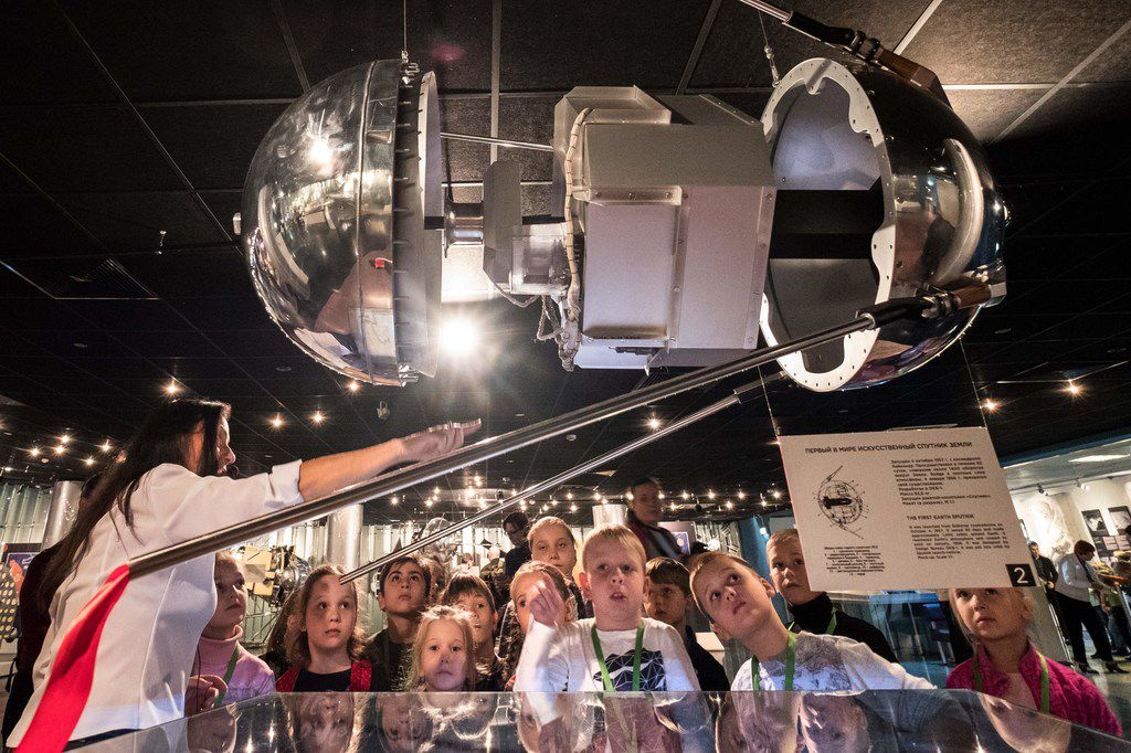Children listen to a guide as they gather near a full-scale replica of the world's first artificial satellite Sputnik, launched by the Soviet Union from a testing range in Kazakhstan on October 4, 1957, at the Memorial Museum of Cosmonautics (or Memorial Museum of Space Exploration) in Moscow on October 3, 2017. When the Soviet Union launched the first artificial satellite 60 years ago, it marked both the beginning of man's space exploration and the start of a space race between Moscow and Washington.