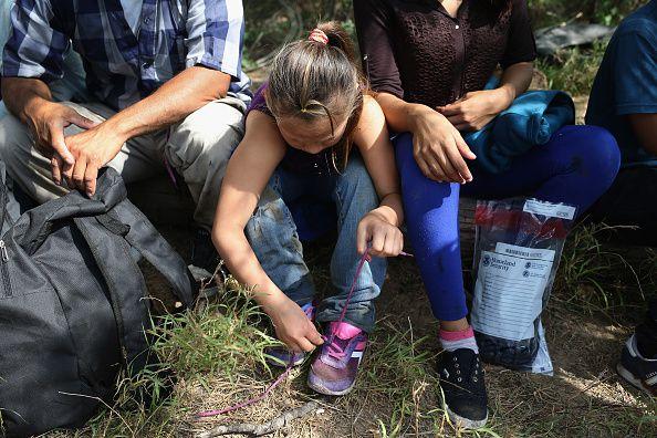 Ania, una niña de 9 años de El Salvador, le quita las trenzas a sus zapatos a pedido de agentes migratorios, luego que su familia cruzó la frontera pidiendo asilo en Estados Unidos, el 14 de abril de este año.