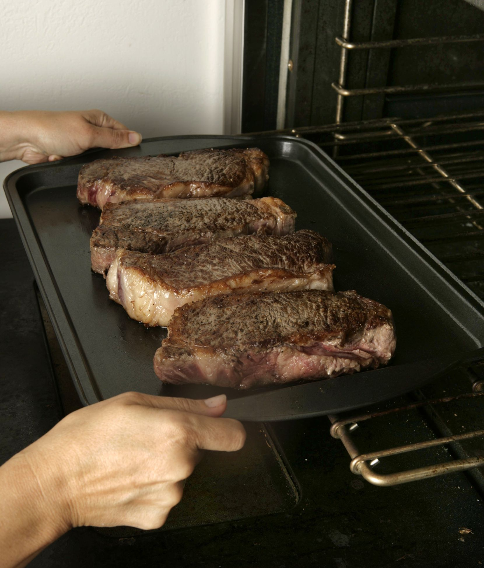 Finishing New York strip steaks in the oven.