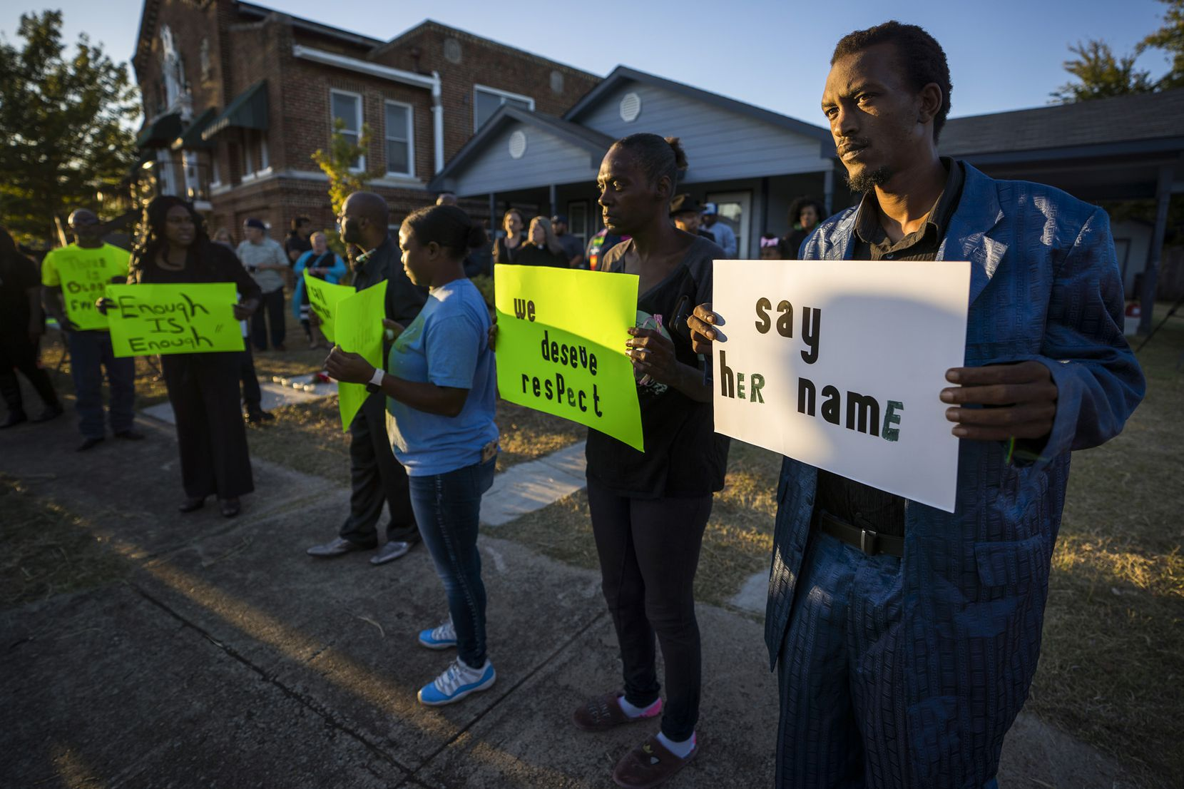Protestors gather outside the house (right) where Atatiana Jefferson was shot and killed, during a community vigil for Jefferson on Sunday, Oct. 13, 2019, in Fort Worth, Texas.  Jefferson, a 28-year-old black woman, was shot in her home by a white Fort Worth police officer during a welfare check.