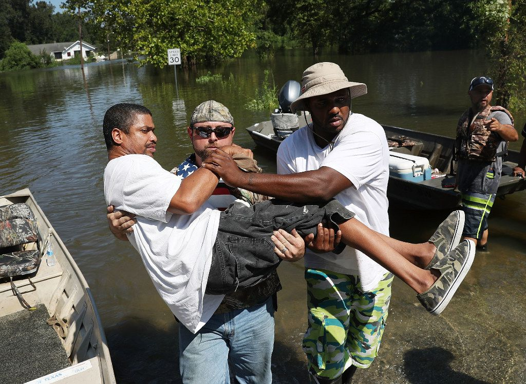 Quintin Sanders is carried to dry land by volunteer rescuers after his neighborhood was inundated with the flooding from Hurricane Harvey.