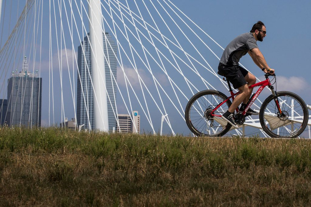 A cyclist passes the Margaret Hunt Hill Bridge while riding on the Trinity Skyline Trail on Tuesday, June 5, 2018, in Dallas.