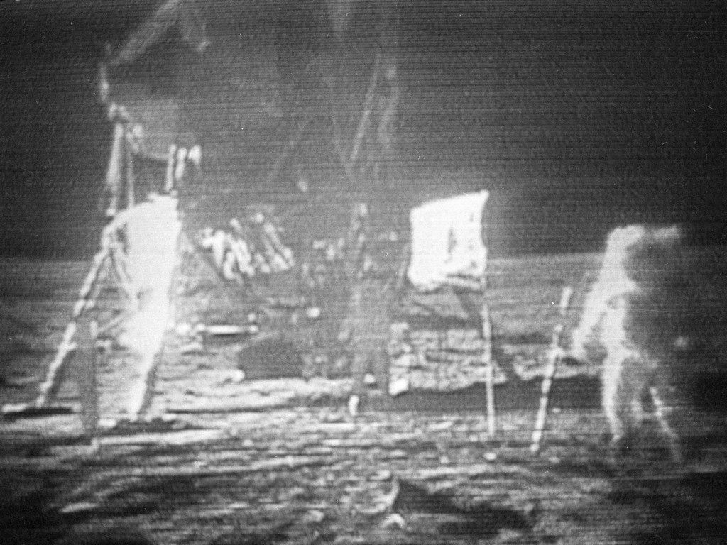 In this July 20, 1969 image made from television, Apollo 11 astronaut Neil Armstrong, right, trudges across the surface of the moon leaving behind footprints. The U.S. flag, planted on the surface by the astronauts, can be seen between Armstrong and the lunar module. Edwin E. Aldrin is seen closer to the craft. The men reported the surface of the moon was like soft sand and they left footprints several inches deep wherever they walked.