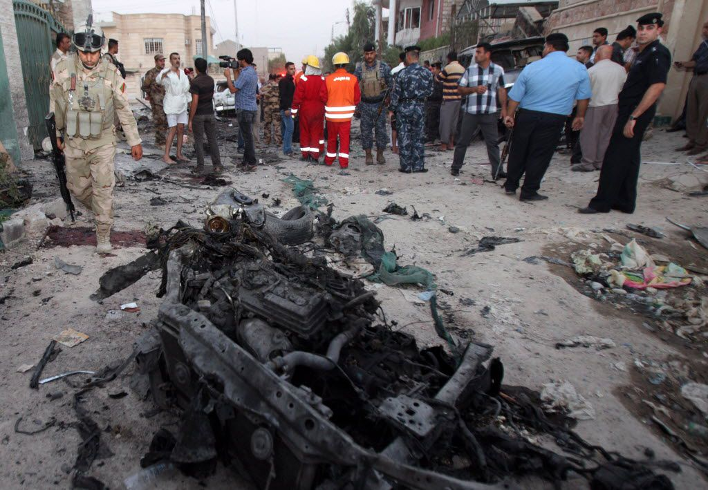 In this picture taken on Sunday, July 14, 2013, security forces inspect the scene of a car bomb attack in Basra, Iraq. Ramadan is shaping up to be the deadliest in Iraq since a bloody insurgency and rampant sectarian killings had the country teetering on the edge of civil war more than half a decade ago.