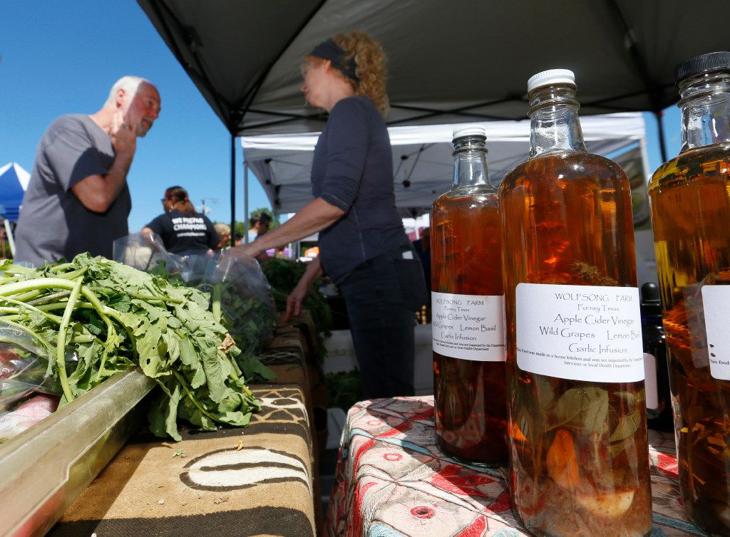 David Nethrery (left) visits with Cyndi Vazquez of Wolfsong Farm at the White Rock Lake Farmers Market. Wolfsong Farm is known for their flavored vinegars and herbal teas made with Texas herbs.