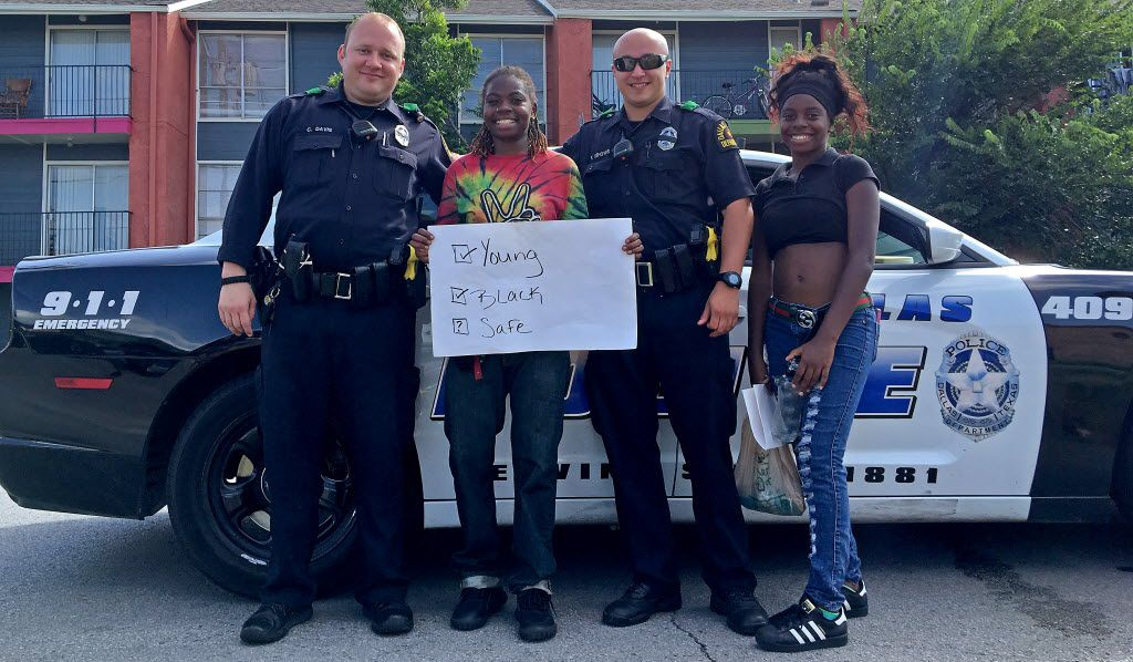 Sisters Naquinta King (second from left) and Azariah King (right) pose for a photograph with Dallas Police Officers C. Davis (left) and P. Dehoyos after they attended a Black Lives Matter protest in Dallas, Sunday, July 10, 2016. The officers would not give their first names. (Jae S. Lee/The Dallas Morning News)