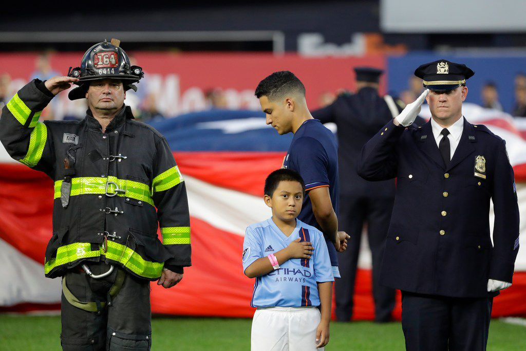 New York City FC's Tony Rocha, center, pauses as a firefighter, left, and police officer, right salute during the playing of the national anthem before an MLS soccer match against Toronto FC Wednesday, Sept. 11, 2019, in New York. (AP Photo/Frank Franklin II)