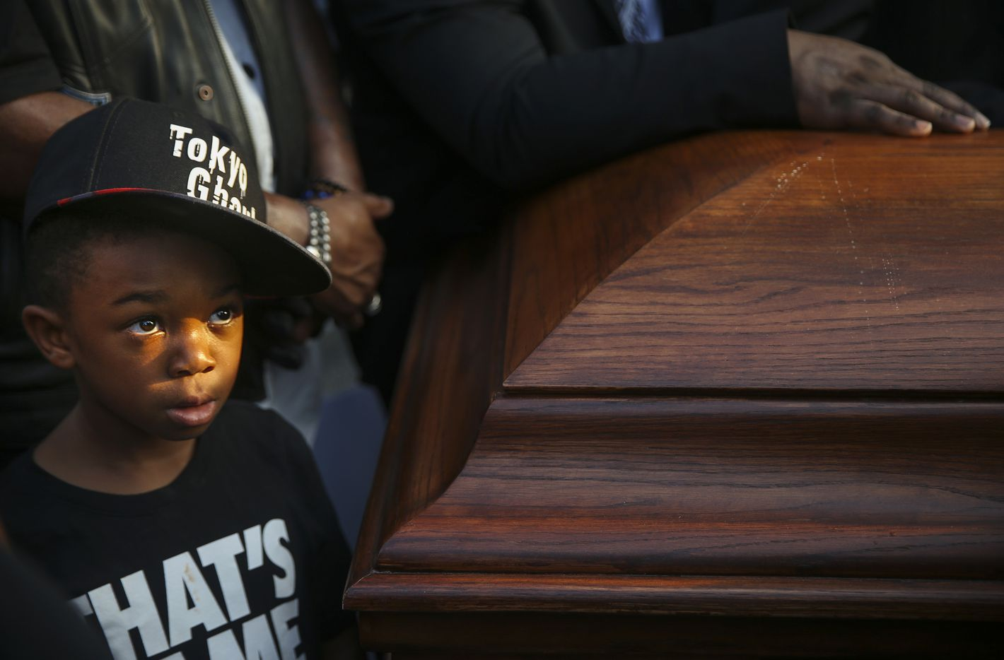 King Solomon Grayson, 6, of Duncanville, Texas, stands near two empty coffins symbolizing the double-murder of black victims' bodies and their names during a protest prior to the start of the Dallas Cowboys' game against the New York Giants on Sunday, Sept. 16, 2018 at AT&T Stadium in Arlington, Texas. The demonstration comes after Botham Jean Shem was shot in his home by Dallas police officer Amber Guyger.