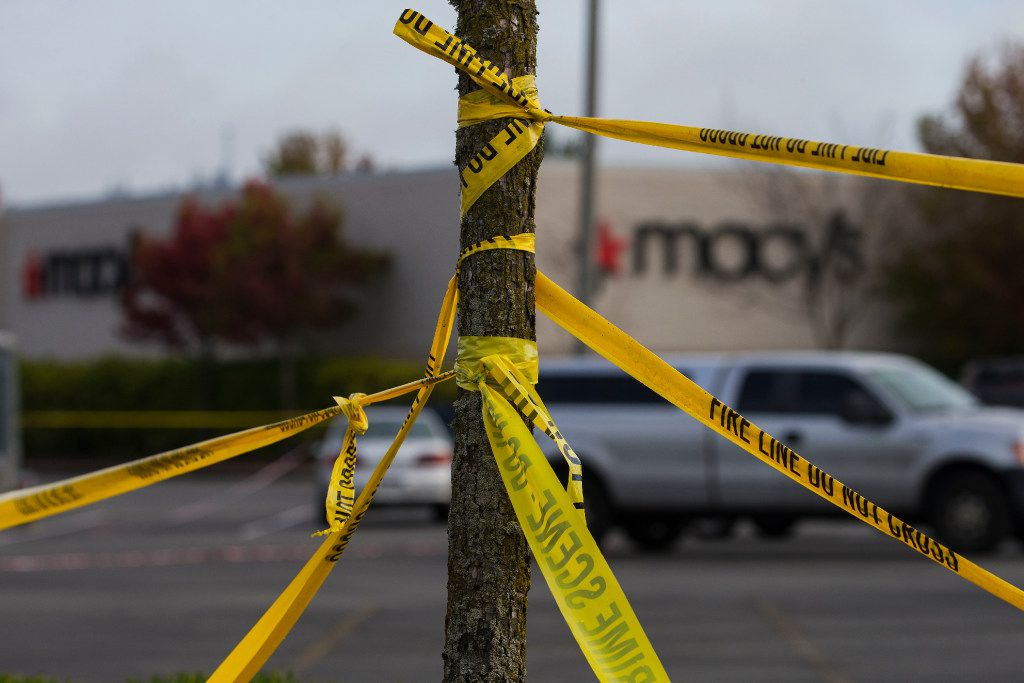 Police tape circled a tree outside the Macy's at Cascade Mall in Burlington, Wash.