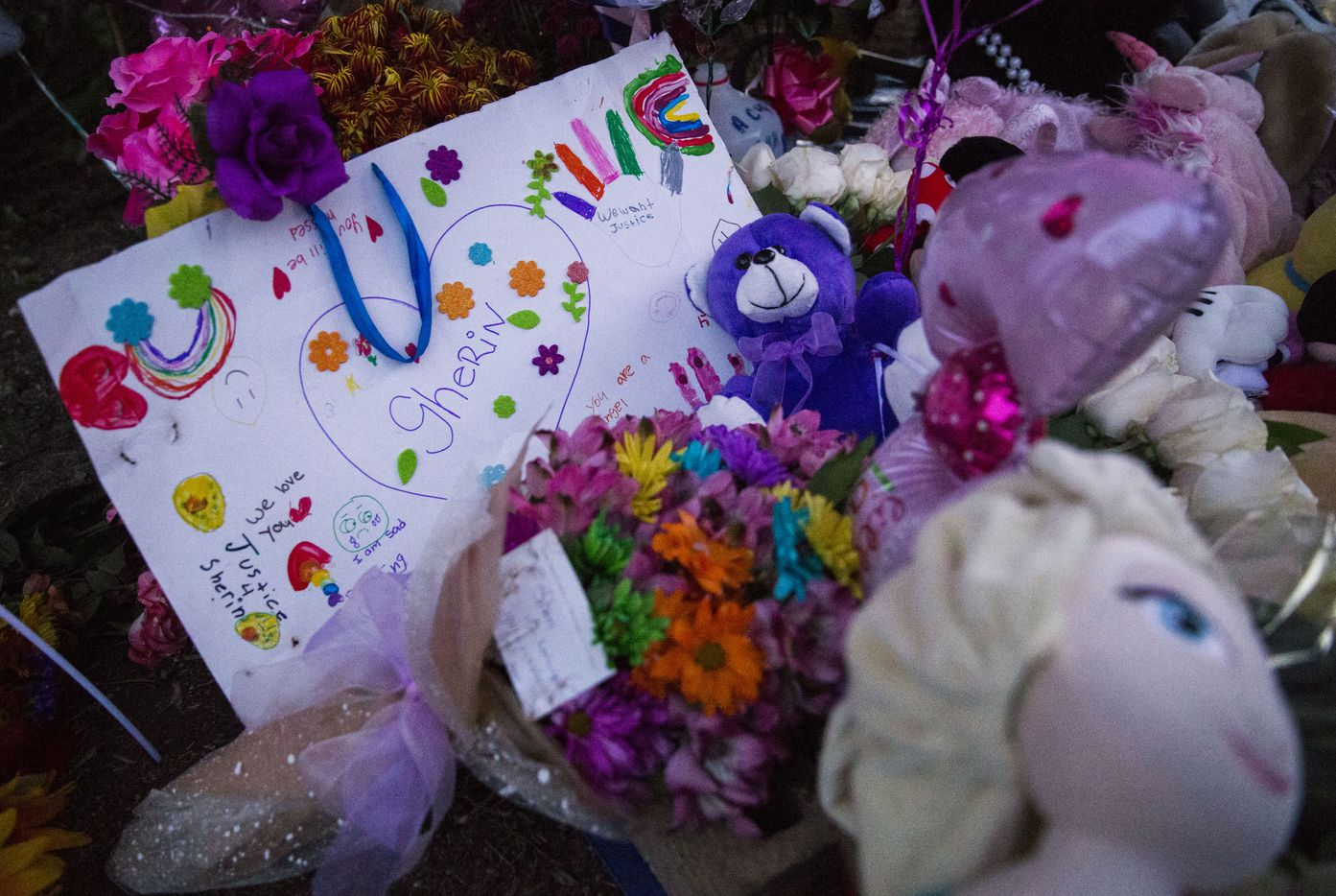 Signs, flowers and other items collect at a memorial for missing 3-year-old Sherin Mathews on Sunday at a tree behind her home.
