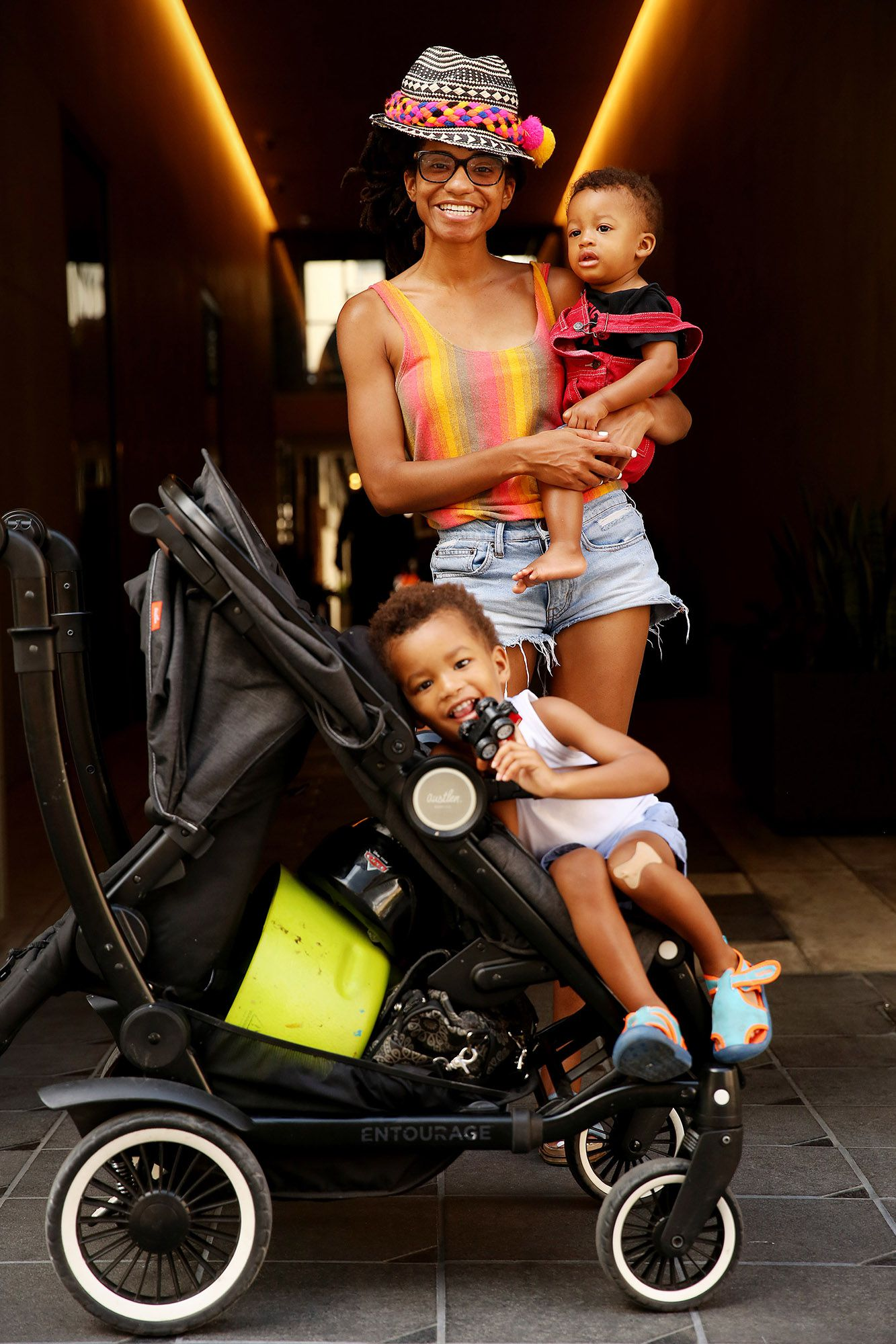 Kenya MomPremier of Dallas holds her son Kemet MomPremier, nine months old, while her other son Miken MomPremier, 2, sits in a stroller during a photograph in the alley connecting Commerce and Main streets on July 11.