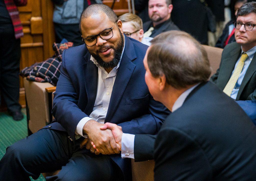 State Representative Eric Johnson of Dallas, left, shakes hands with Bruce Bugg, Chairman of the Texas Transportation Commission, before the State Preservation Board voted to remove a Children of the Confederacy plaque that is displayed in the Texas state capital on the fourth day of the 86th Texas legislature on Friday, January 11, 2019 at the Texas state capital in Austin, Texas.