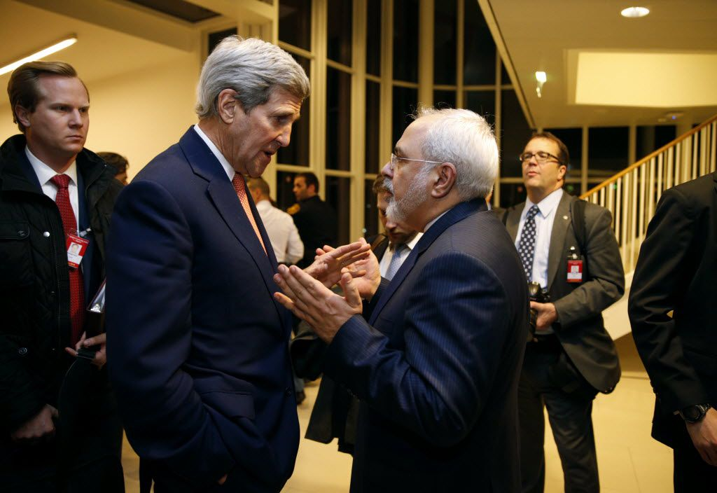 U.S. Secretary of State John Kerry talks with Iranian Foreign Minister Mohammad Javad Zarif, right, after the International Atomic Energy Agency (IAEA) verified that Iran has met all conditions under the nuclear deal, in Vienna, Saturday Jan. 16,  2016. (Kevin Lamarque/Pool via AP)