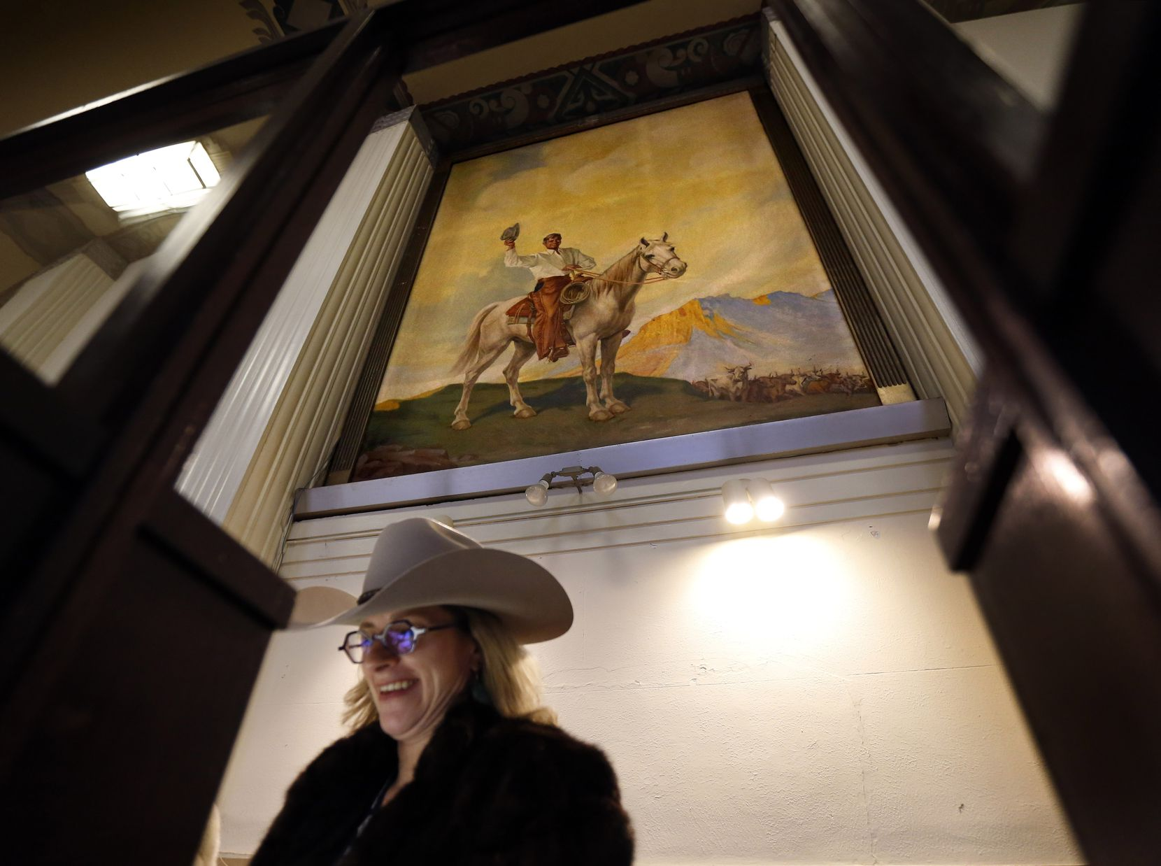 Junior League of Fort Worth member Claudia Thompson works in the old ticket booth below a 12x16 foot painting of Will Rogers on his horse, 'Soapsuds' in the north entryway of Will Rogers Memorial Coliseum, Wednesday, January 30, 2019 at the Fort Worth Stock Show and Rodeo in Fort Worth.