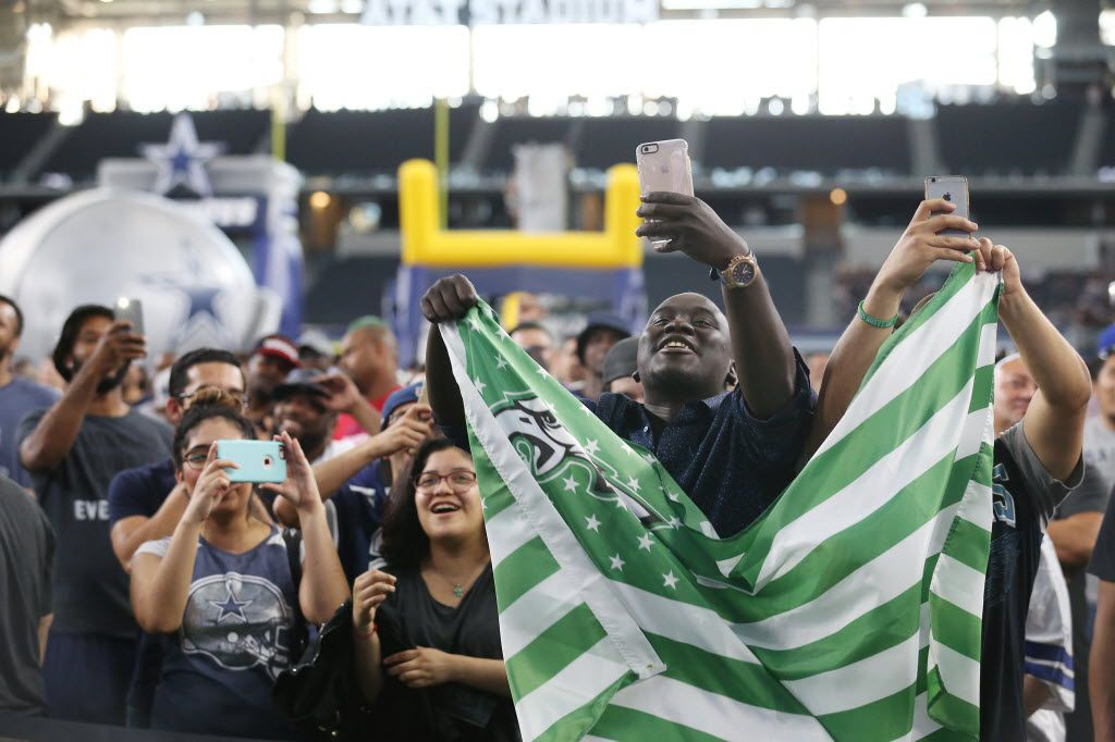 Philadelphia Eagles fans Samea Sey (second from right) and Jose Pulido (covered with flag), both of Dallas, celebrate after the Eagles picked Carson Wentz during a watch party before the Dallas Cowboys pick running back Ezekiel Elliott, of Ohio State, in the first round of the 2016 NFL Draft at AT&T Stadium in Arlington, Texas Thursday April 28, 2016. (Andy Jacobsohn/The Dallas Morning News)