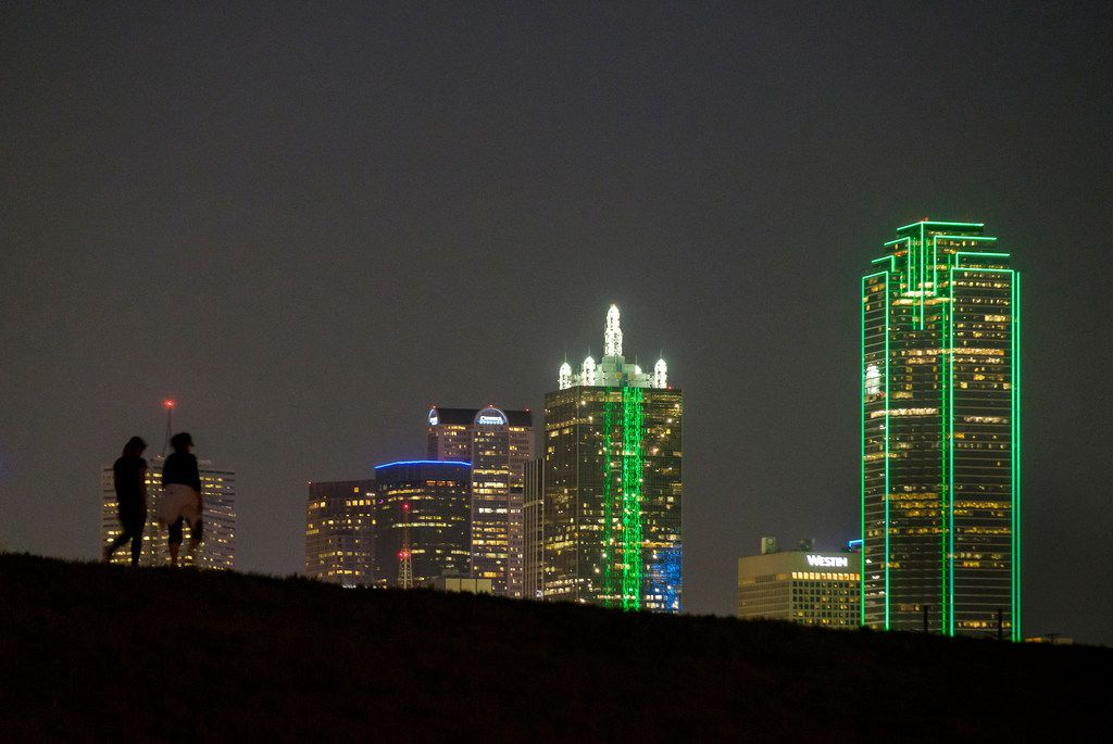 The downtown skyline lights up behind walkers on the Trinity Skyline Trail on Thursday, April 4, 2019, in Dallas.