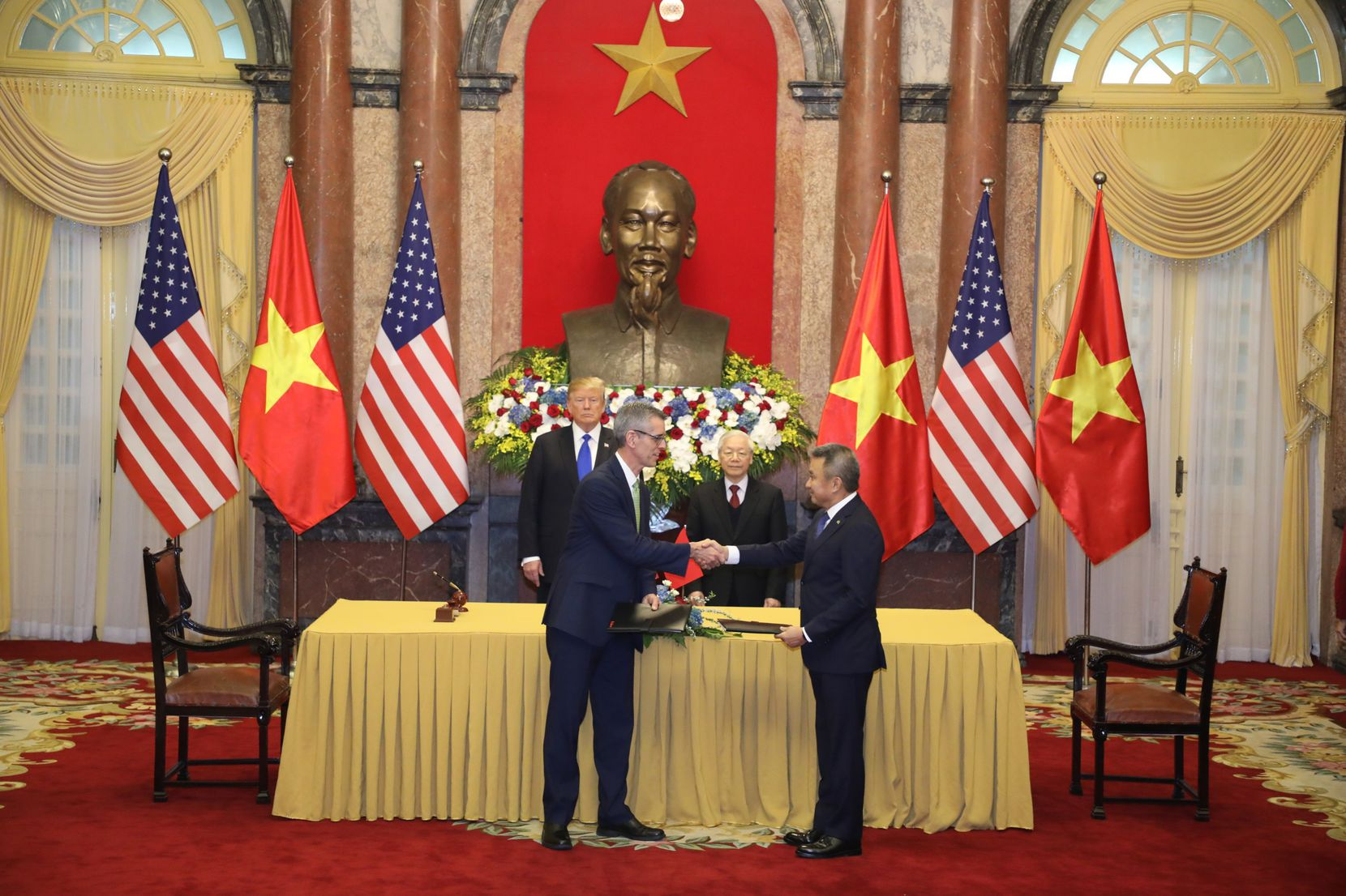 Sabre executive Dave Shirk shakes hands with Vietnam Airlines CEO Duong Tri Thanh during Wednesday's ceremonial signing session in Hanoi as part of President Trump's summit with his counterpart in Vietnam.