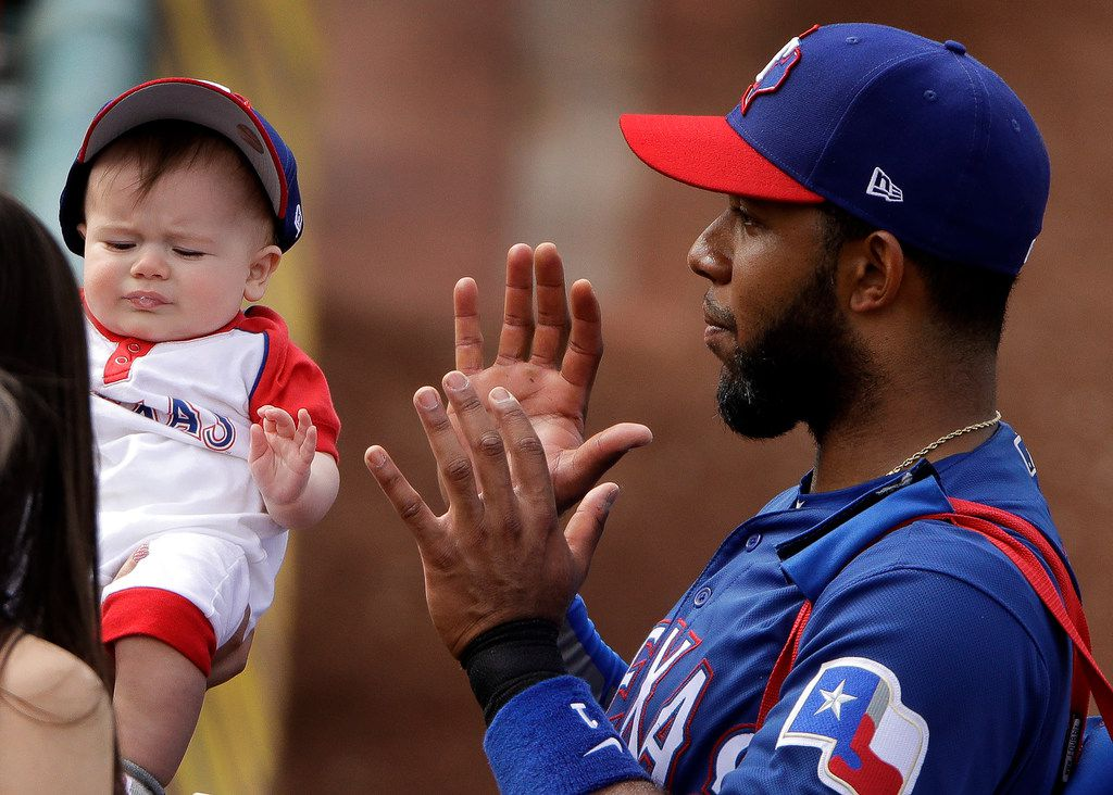 Texas Rangers' Elvis Andrus poses with a baby as he leaves field after the fifth inning of a spring training baseball game against the Chicago White Sox Friday, March 1, 2019, in Surprise, Ariz. (AP Photo/Charlie Riedel)
