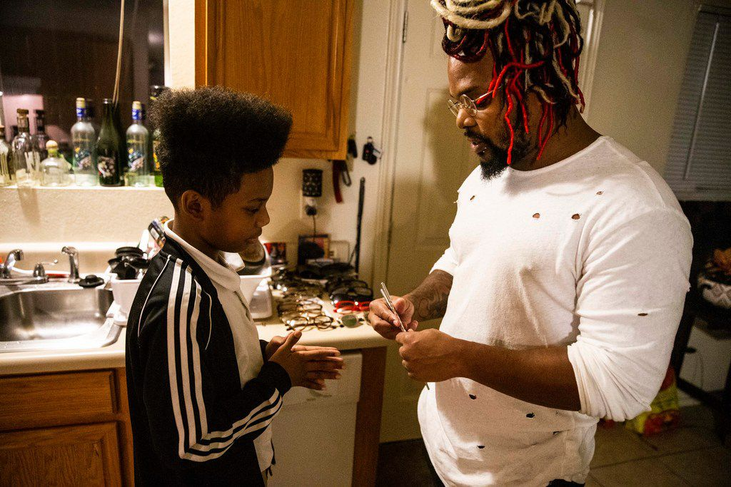 Dorelle Harrison teaches his son, Prince Harrison, how to use chopsticks in his Dallas home on Jan. 15, 2019. Harrison works for the Environmental Protection Agency as a physical scientist. Due to the government shutdown, Harrison was furloughed and has not been working.