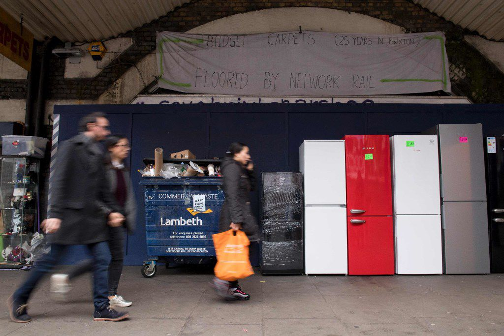 A picture shows people walking past a boarded up commercial unit in the viaduct arches near to Brixton railway station in south London on December 19, 2016.  Local residents, traders and volunteers in the south London neighborhood of Brixton are fighting a new wave of gentrification that they fear will sanitize its vibrant streets and destroy livelihoods. Their anger is focussed on railway operator Network Rail, which owns a series of viaduct arches that run through the heart of the traditionally Afro-Caribbean district, and the shops that have thrived therein. The operator has started to refurbish the units on Atlantic Road and Brixton Station Road, on either side of the railway, with around 20 independent stalls and eateries being boarded up since October.