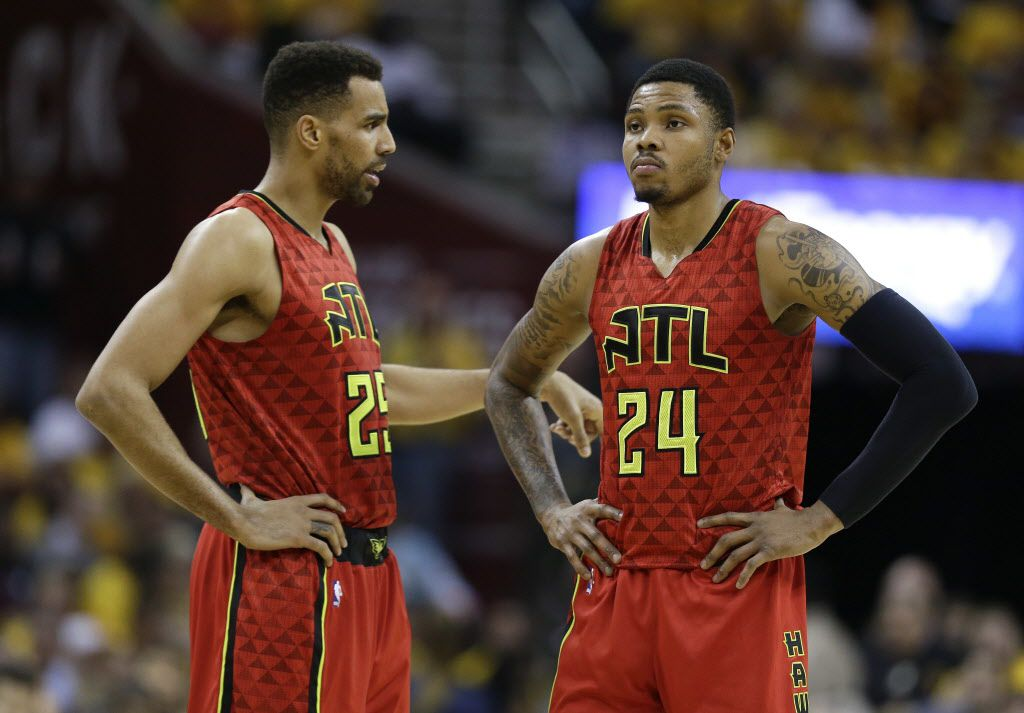 Atlanta Hawks forward Thabo Sefolosha (25) talks with forward Kent Bazemore (24) during a break in play in the first half against the Cleveland Cavaliers during Game 2 of a second-round NBA basketball playoff series, Wednesday, May 4, 2016, in Cleveland. (AP Photo/Tony Dejak)