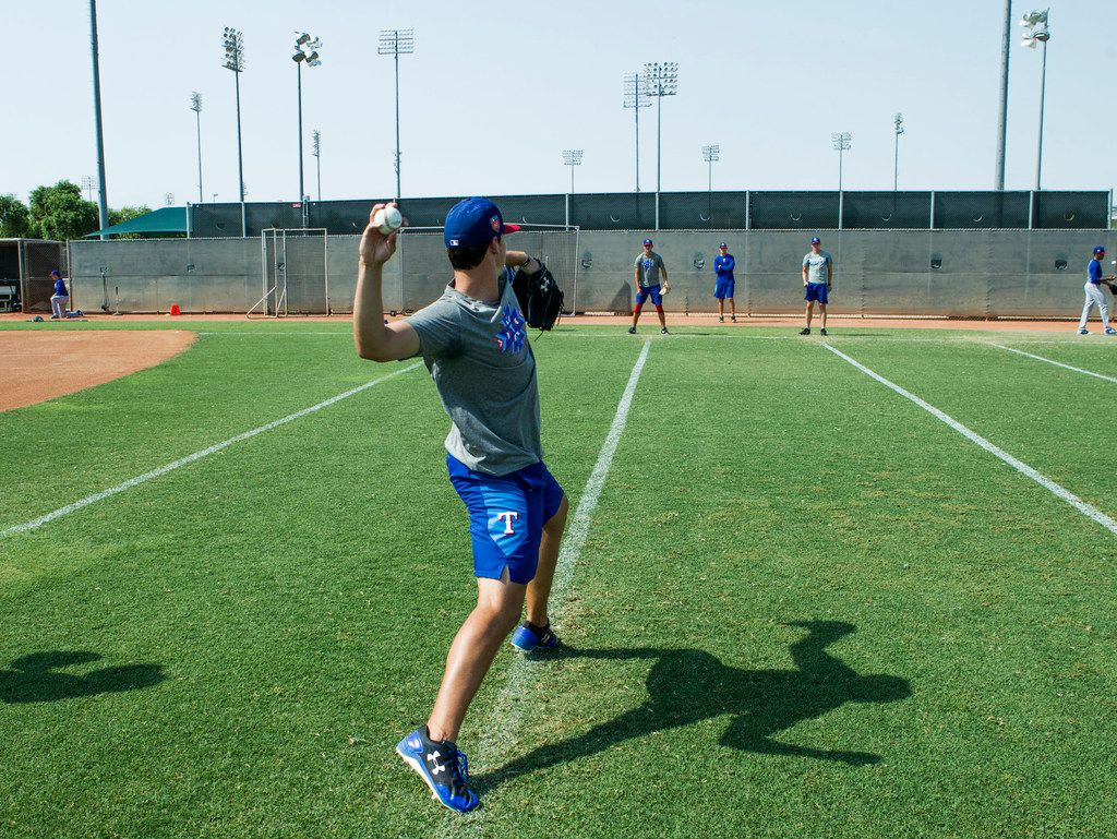 """Texas Rangers' pitcher Cole Winn works on his delivery while doing a little long toss with teammate Owen White at Rangers' training facility Thursday, Aug. 9, 2018 in Surprise, Arizona. The players are learning from a program that is designed to hopefully prevent injury, part designed to allow for more learning of """"feel"""" for the game.(Darryl Webb/Special Contributor)"""