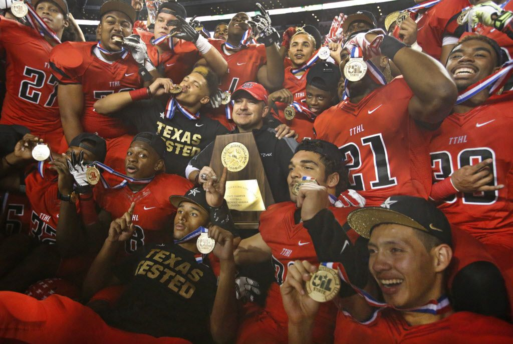 Cedar Hill head coach Joey McGuire is surrounded by his players as they pose with the trophy after their 23-20 win during the 6A-II state championship game between Cedar Hill High School Longhorns and Katy High School Tigers at AT&T Stadium in Arlington on Saturday, December 20, 2014.  (Louis DeLuca/The Dallas Morning News) 12212014xSPORTS2