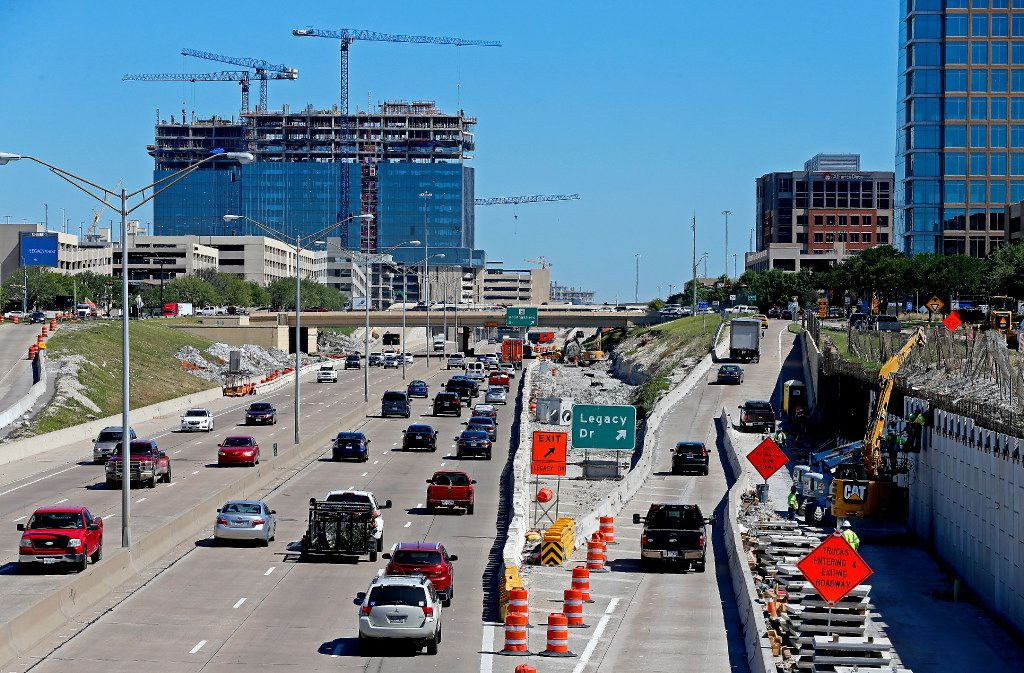 Traffics move on Dallas North Tollway as the new Toyota headquarters is under construction in the background in Plano.