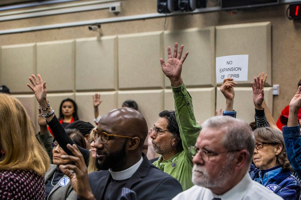 "People raise their hands and one citizen holds up a ""No expansion of CPRB"" sign as the Dallas Police Department presents recommendations for the Citizens Police Review Board to Dallas City Council at Dallas City Hall in Dallas on Feb. 11, 2019. Members of the Dallas-based political group Citizens Matter, which strongly opposed the removal of the city's Confederate monuments, showed up at Monday's meetings with signs that read ""No expansion of CPRB."""