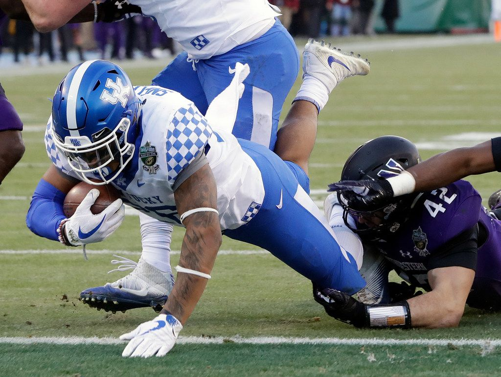 Kentucky running back Benny Snell Jr., left, gets past Northwestern defender Paddy Fisher (42) to score a touchdown on a 3-yard run in the first half of the Music City Bowl NCAA college football game Friday, Dec. 29, 2017, in Nashville, Tenn. (AP Photo/Mark Humphrey)
