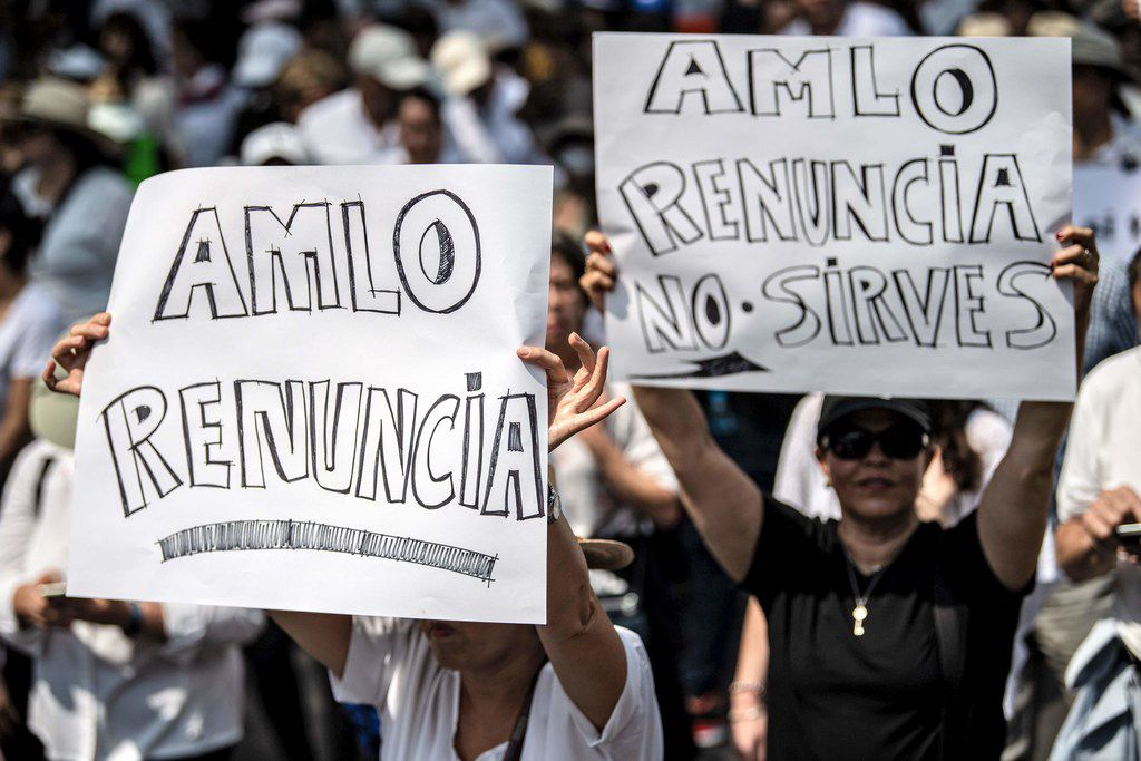 """People take part in the so-called """"March of Silence"""" against Mexican President Andres Manuel Lopez Obrador's policies with signs reading """"AMLO resign"""" in Mexico City, on May 5, 2019."""