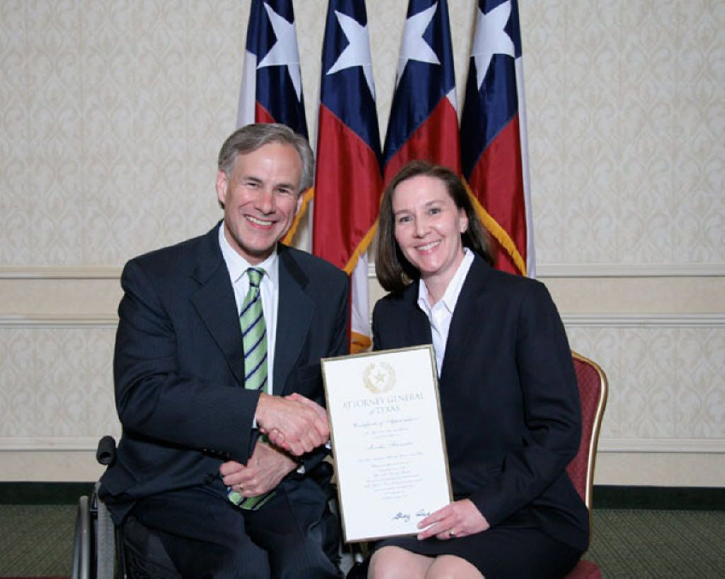 As attorney general in 2008, Greg Abbott presented Martha Fitzwater Pigott with an award. Fitzwater Pigott's attorney said his client was fired after she raised concerns that the attorney general's office was breaking federal rules as it tried to renew a contract with tech giant Accenture.