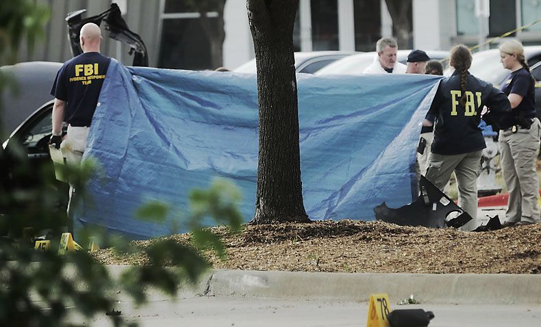 A tarp shields the view Monday morning of the car driven by two men killed Sunday in Garland after they opened fire outside a contest for cartoons depicting the Muslim prophet Muhammad. The car was dismantled to ensure that it was not carrying explosives.