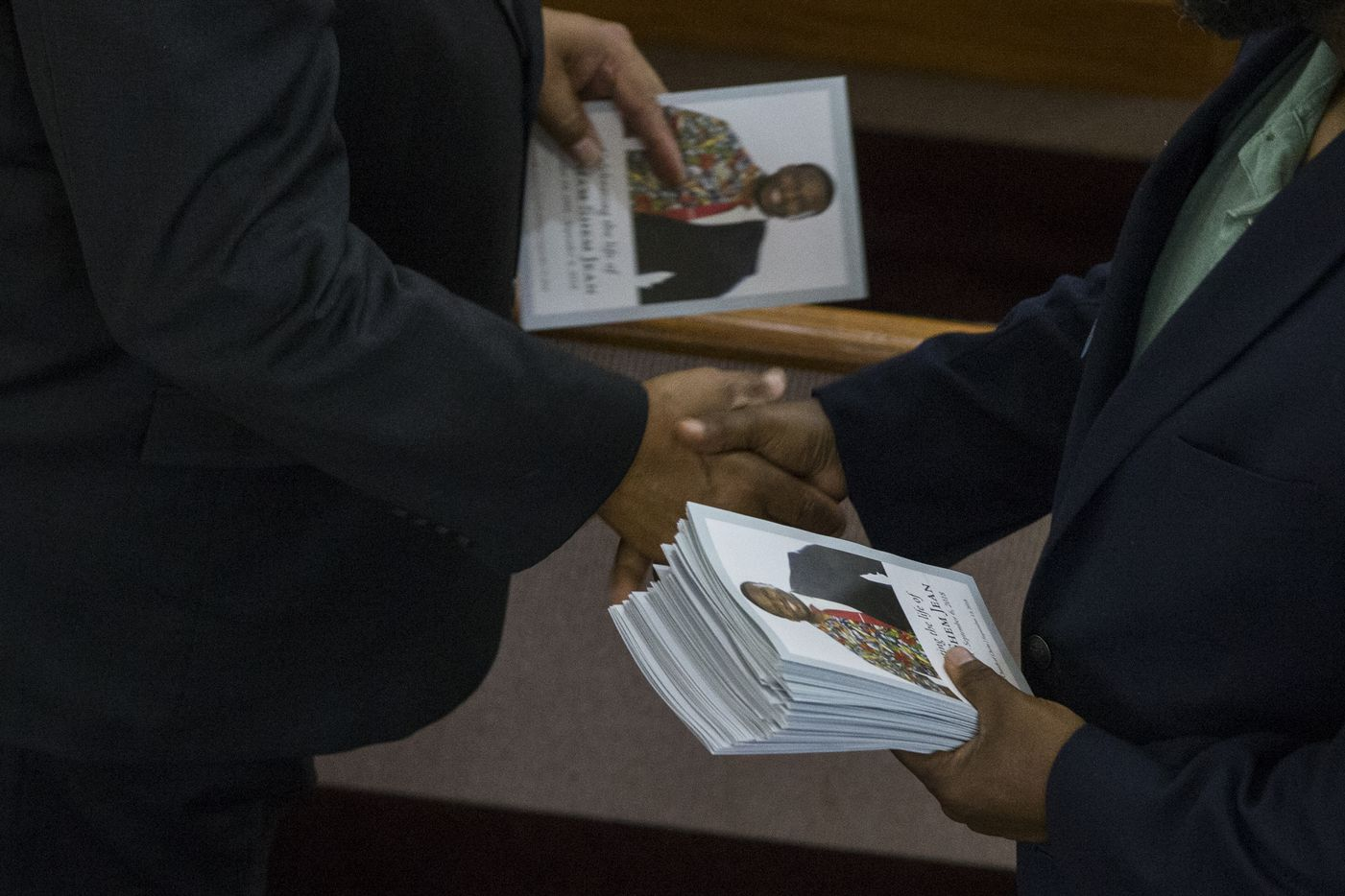 An usher shakes a mouners' hand after handing him a program before the funeral service for Botham Shem Jean at the Greenville Avenue Church of Christ on Thursday, September 13, 2018 in Richardson, Texas. He was shot and killed by a Dallas police officer in his apartment last week in Dallas. (Shaban Athuman/ The Dallas Morning News)