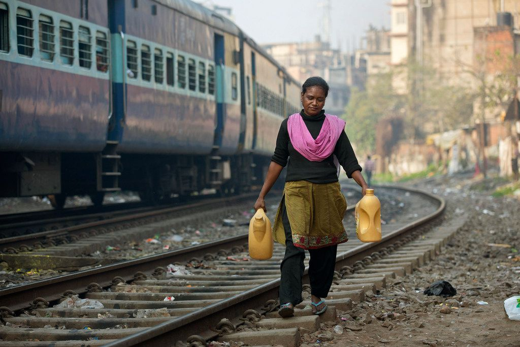 A woman who lives near the railway tracks fetches drinking water in plastic containers in Gauhati, India.
