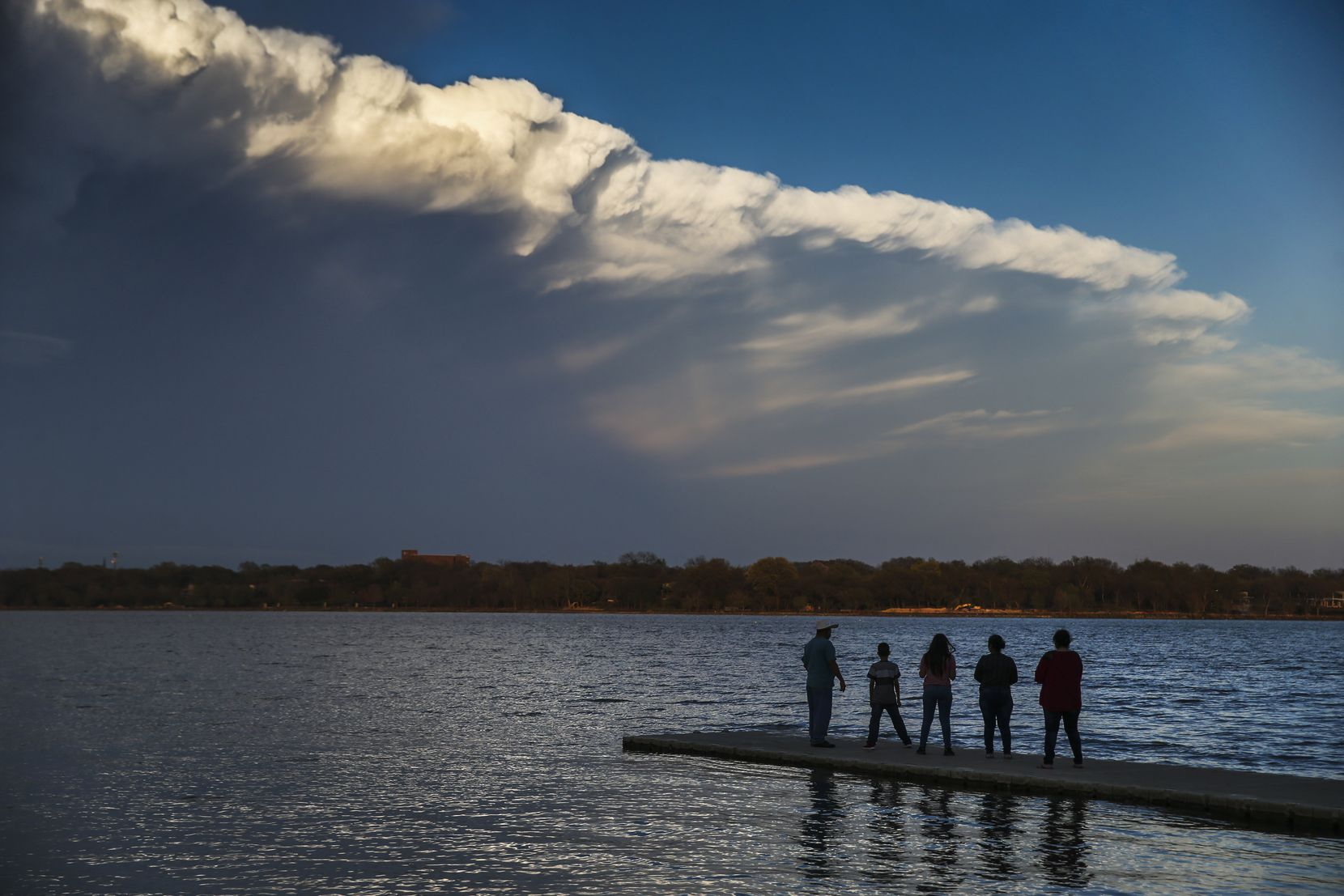 People watch passing clouds from a dock at White Rock Lake on Sunday afternoon, March 24, 2019.
