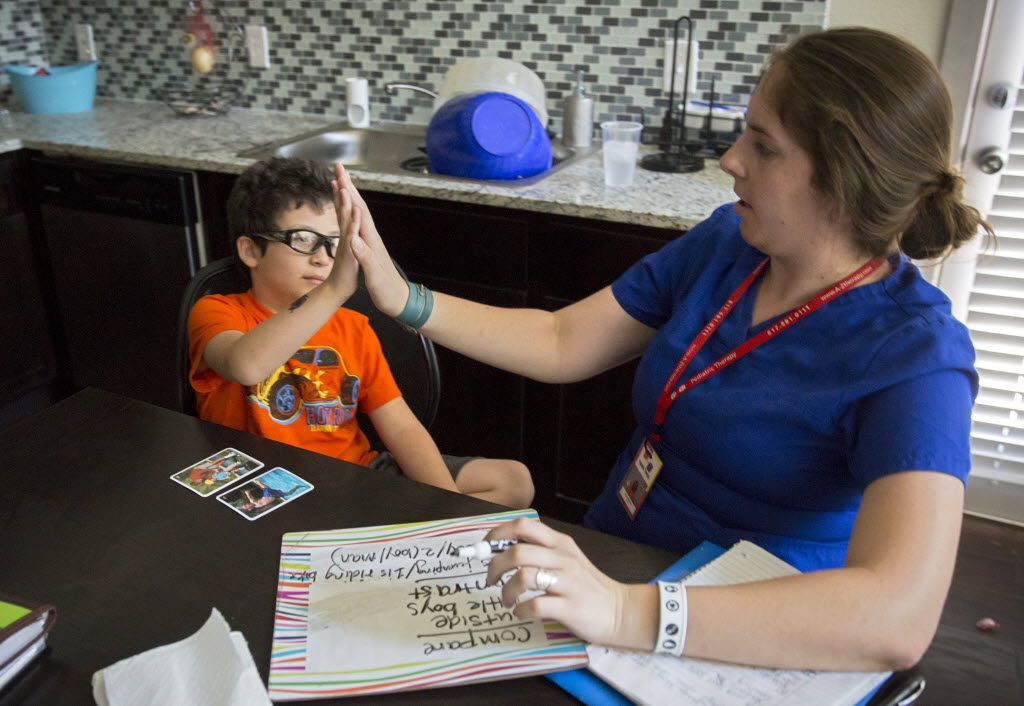 Jacob Casablanca (left) high-fives speech therapist Elizabeth Price during their session last month in Hurst. Jacob, 7, is autistic and suffers from speech delays.