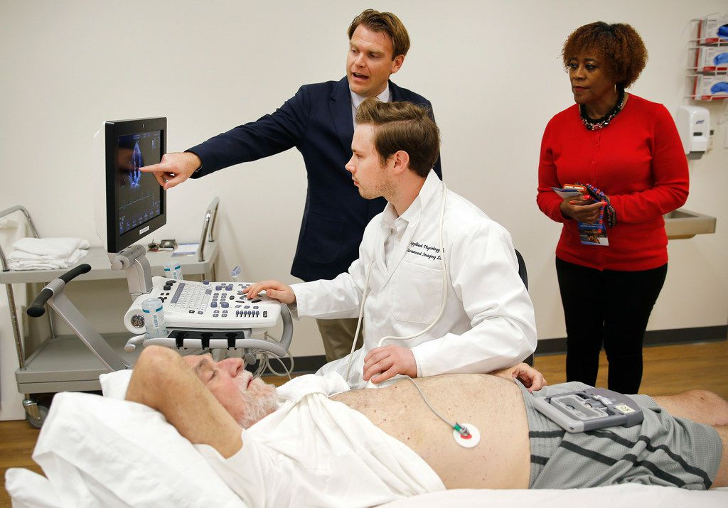 Michael D. Nelson, Applied Physiology and Advanced Imaging Laboratory director, pointing at screen, shows Phyllis Miller how PhD student Jake Samuel is performing an ultrasound reading on volunteer Bill McNeill's heart during a tour at the University of Texas-Arlington this fall.