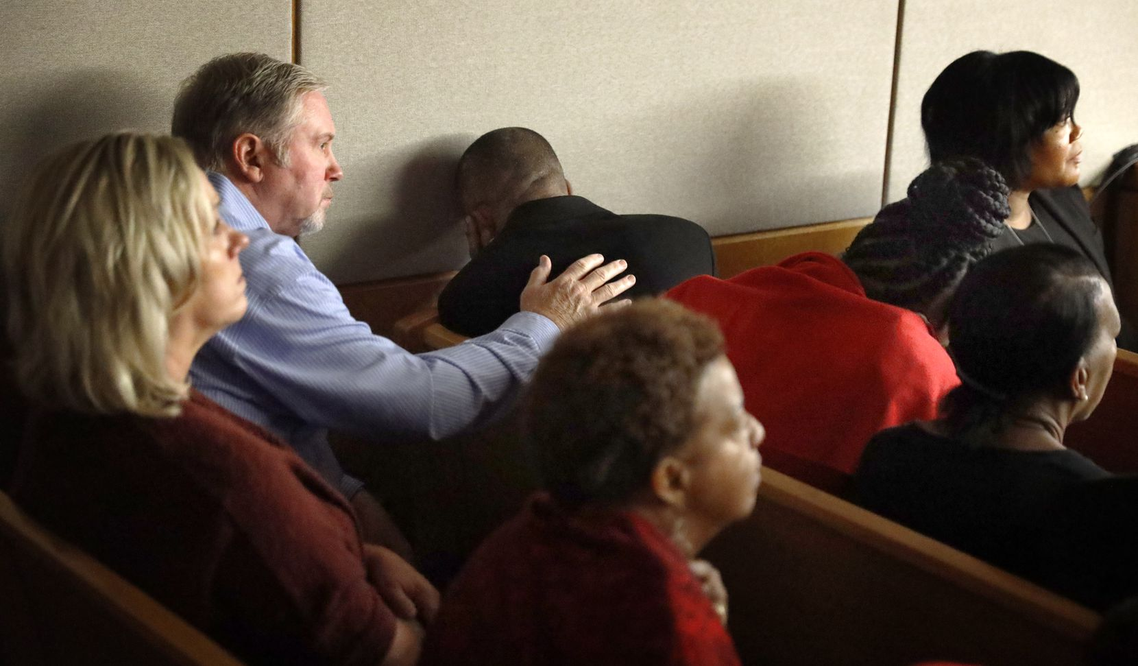 Outside the presence of the jury, Botham Jean's father, Bertrum Jean (center), leans his head away and covers his ears as the police body camera footage is shown inside the courtroom.