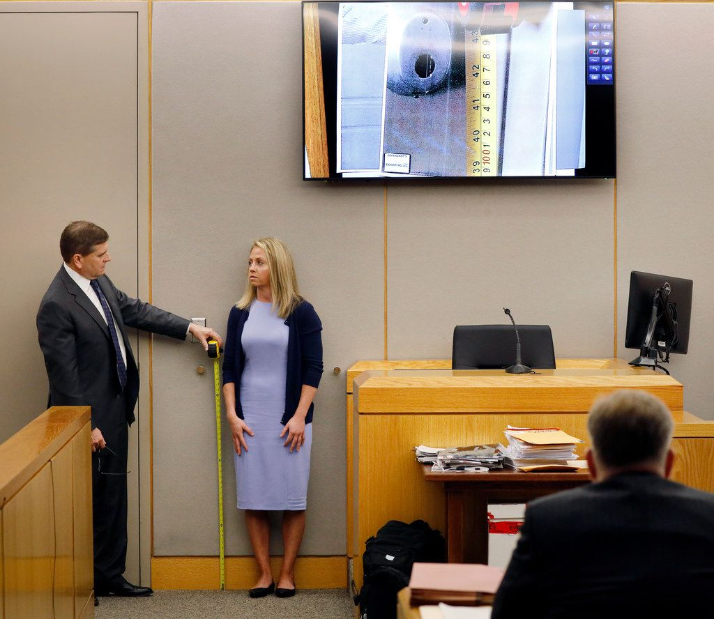 Defense attorney Toby Shook measures the height of a keyhole beside Amber Guyger during testimony Friday in her murder trial. (Tom Fox/Staff Photographer)