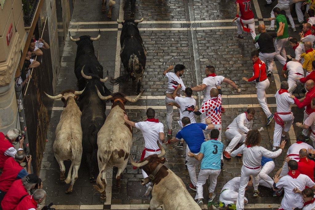 Revellers run with Puerto de San Lorenzo's fighting bulls along Calle Estafeta during the second day of the San Fermin Running of the Bulls festival on July 7, 2018 in Pamplona, Spain.