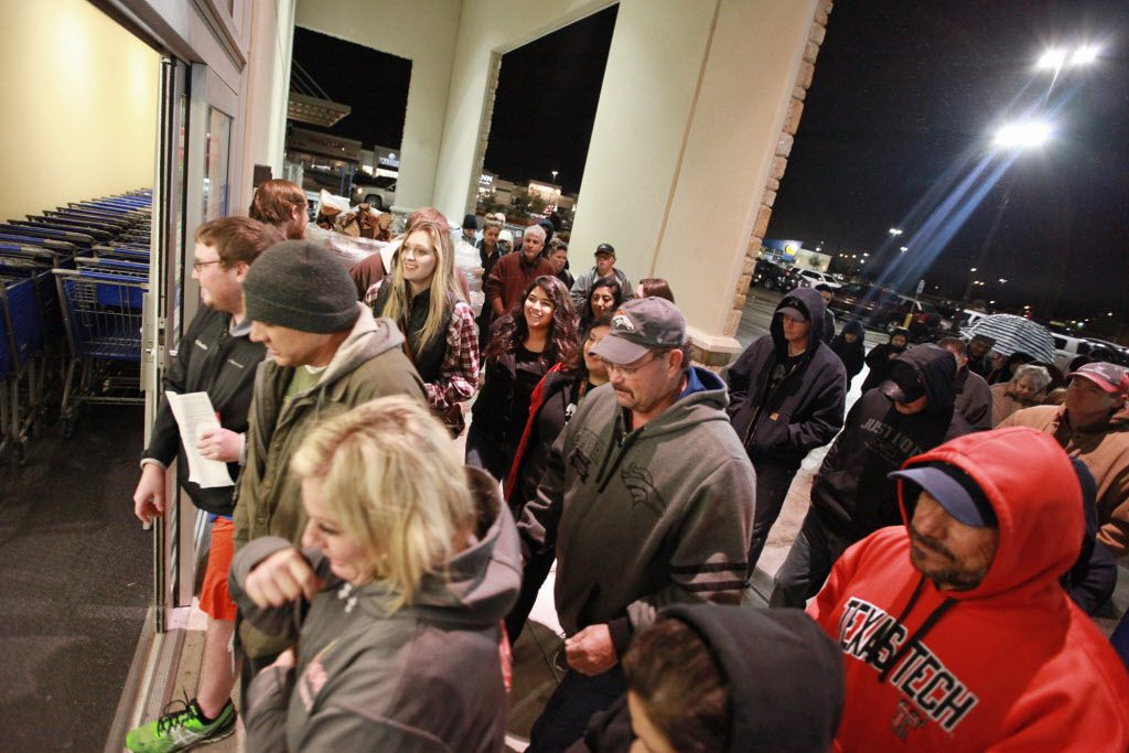 Shoppers rush through the entrance to the Academy Sports+Outdoors at 5:00 a.m. in the Chimney Rock Shopping Center on Friday, Nov. 27, 2015, in Odessa, Texas.