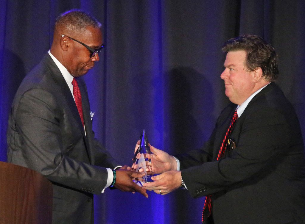 AT&T Chief Compliance Officer David Huntley, left, accepts an ethics award from Michael Webb, chairman of the North Texas Ethics Association, right, at the 18th annual Greater Dallas Business Ethics Award luncheon in Dallas. Three hours later, AT&T's involvement in Michael Cohen's shell company was revealed.