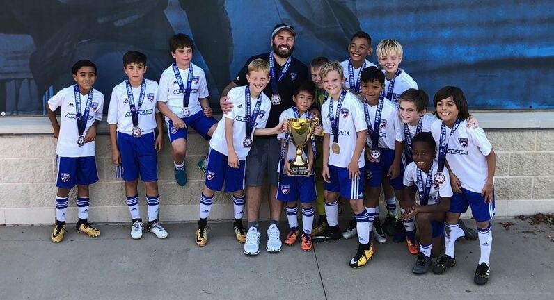FC Dallas 07B Central Blue pose with the Bobby Rhine Invitational U11 Championship trophy.