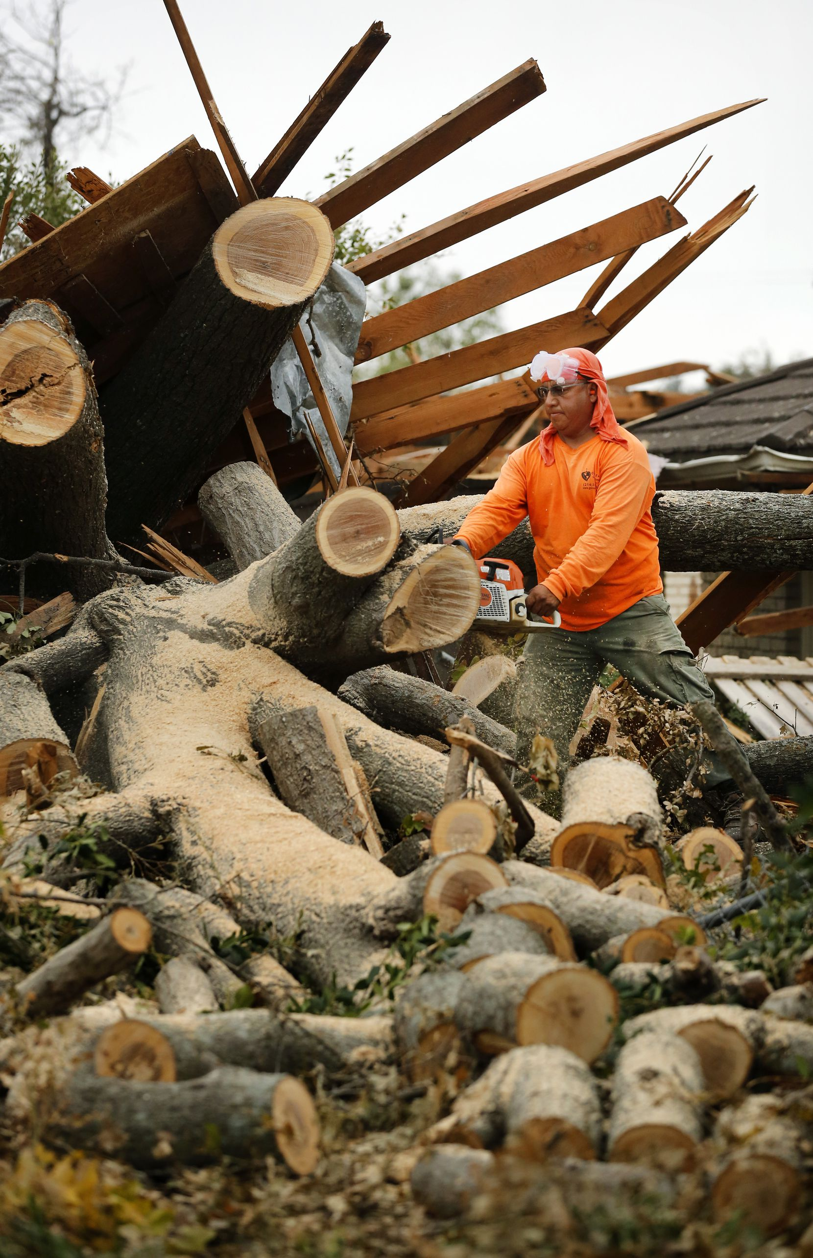 Landscaper Bartolo Bautista used a chainsaw to remove a toppled tree from a home on Lavendale Avenue in North Dallas last week.