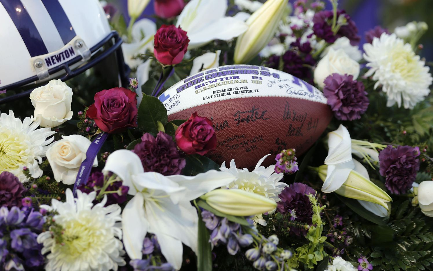 """Signed football with the December 20, 2018 state championship date on it rests on the casket of Newton High School head football coach William Theodore """"W.T."""" Johnston during his memorial service at Curtis Barbay Field at Newton High School in Newton, Texas on Wednesday, May 15, 2019. (Vernon Bryant/The Dallas Morning News)"""