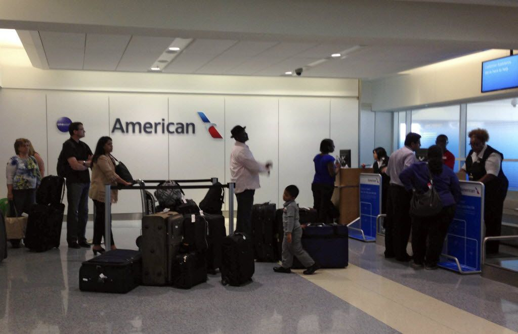 Passengers wait at an American Airlines gate at DFW Airport.