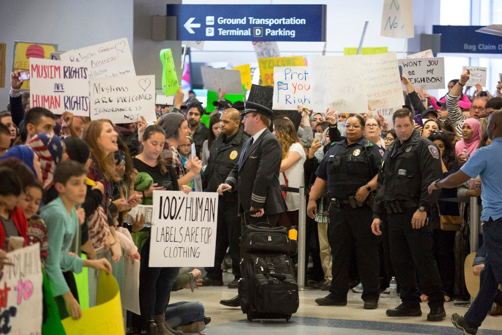 Police keep a walkway clear in the international arrivals hall at DFW International Airport as protestors fill the hall in opposition to President Donald Trump's executive order barring certain travelers on Sunday, Jan. 29, 2017.  (Smiley N. Pool/The Dallas Morning News)