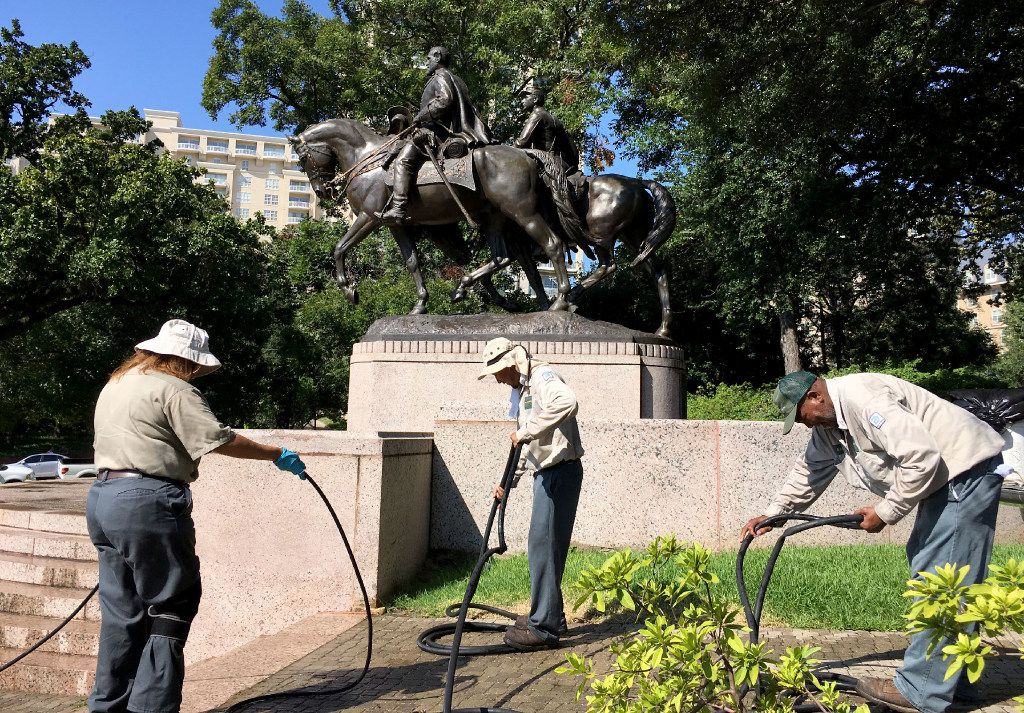 "Dallas Parks department workers packed up after removing graffiti from the Robert E. Lee statue in Lee Park on Aug. 19. One of the workers said the word ""Nazi"" had been painted on the monument to the Confederate general. (Michael Hamtil/Staff Photographer)"