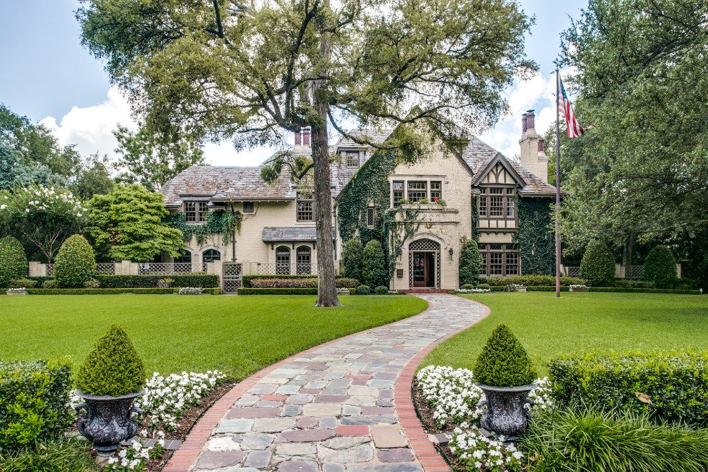 The house of Sam Wyly in Highland Park. Designed by architect C.D. Hill, the 1923 Tudor house features an asymmetrical front gable. Each chimney is capped with terra cotta chimney pots.